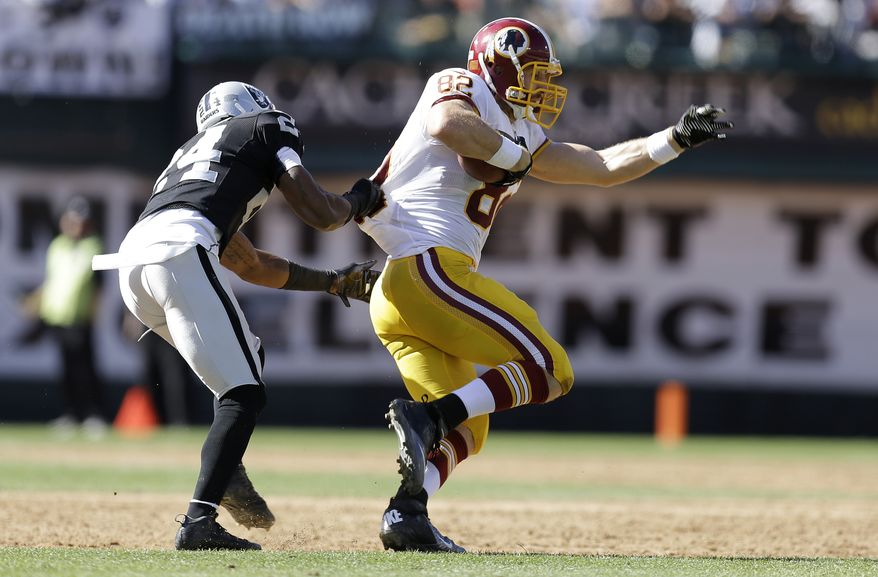Oakland Raiders cornerback Charles Woodson (24) grabs the jersey of Washington Redskins tight end Logan Paulsen (82) during the third quarter of an NFL football game in Oakland, Calif., Sunday, Sept. 29, 2013. (AP Photo/Ben Margot)
