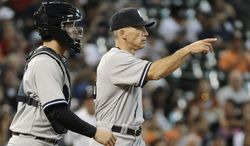 New York Yankees manager Joe Girardi, right, gestures for a new pitcher as he walks out to the mound with catcher J.R. Murphy in the 13th inning of a baseball game against the Houston Astros Sunday, Sept. 29, 2013, in Houston. The Yankees won 5-1 in 14 innings. (AP Photo/Pat Sullivan)