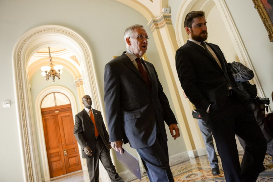 Senate Majority Leader Harry Reid (D-Nev.) speaks with his communications director Adam Jentleson, right, as he heads to a meeting with democratic leaders hours before a Monday night deadline on a government funding bill threatens the first government shutdown in 17 years, Washington, D.C., Monday, September 30, 2013. (Andrew Harnik/The Washington Times)