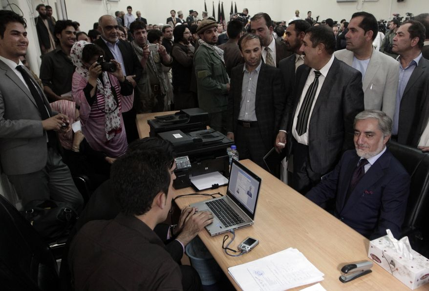 A prominent opposition leader, Abdullah Abdullah, seated right, registers his candidacy in next year's presidential election in Kabul, Afghanistan, Tuesday, Oct. 1, 2013. The presidential election is a key vote that will help determine the success or failure of 12 years of U.S.-led military and political intervention in the country. (AP Photo/Rahmat Gul)