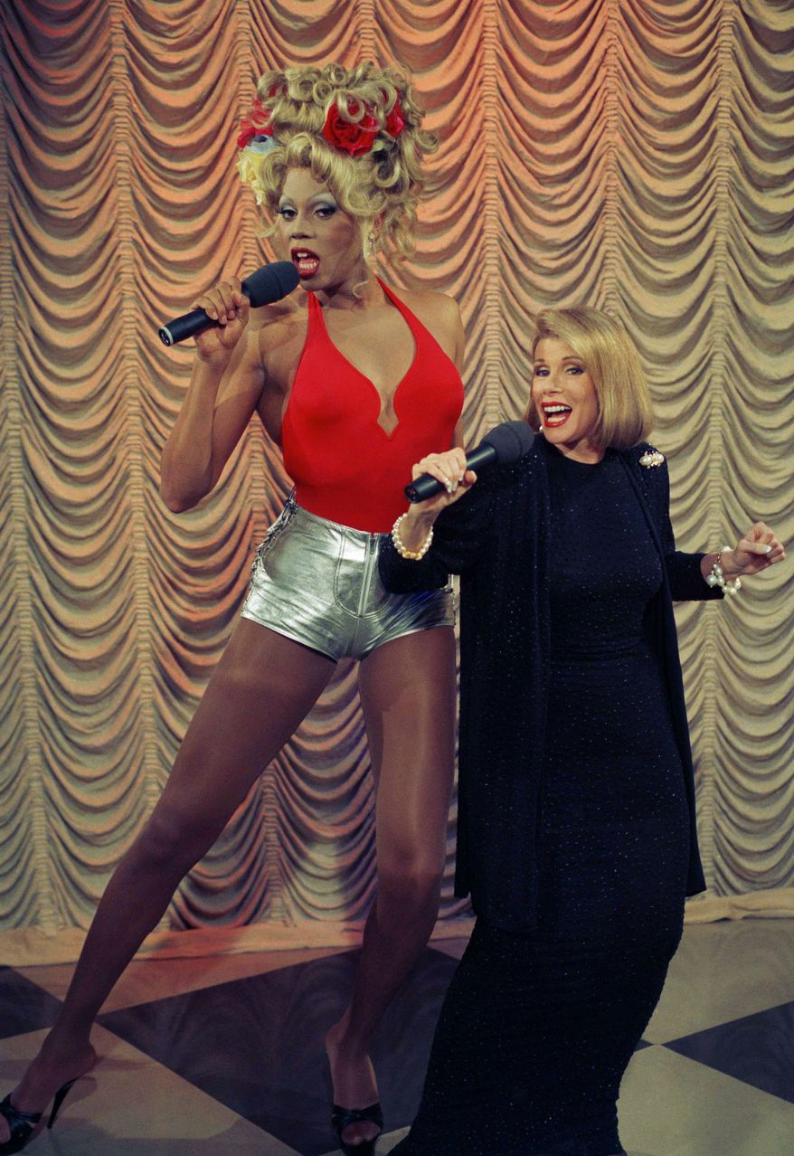 """Entertainer RuPaul, left, sings a number from his debut album """"Supermodel of the World"""" with Joan Rivers during taping of her show in New York, July 28, 1993. The drag queen also discussed his soon-to-be released book """"My Supermodel"""" on the show. (AP Photo/Jim Cooper)"""