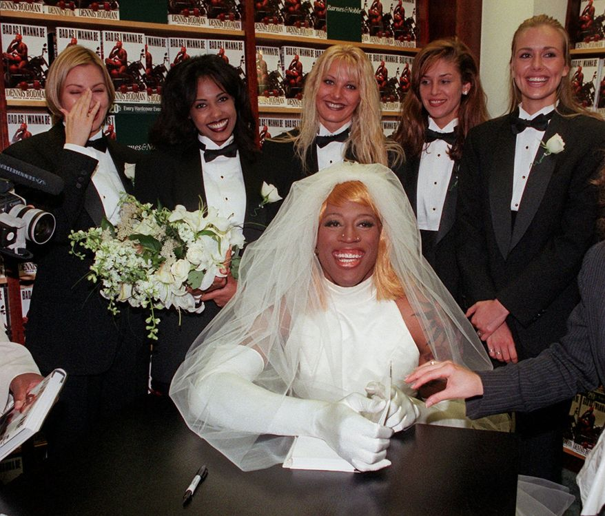 """Chicago Bulls forward Dennis Rodman, dressed as a bride, poses for photographers at a New York bookstore Wednesday, August 21, 1996.  Rodman is promoting his book """"Bad As I Wanna Be."""" (AP Photo/Mark Lennihan)"""