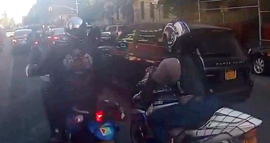 In this frame grab from video provided by the New York Police Department, motorcyclists ride alongside a sport utility vehicle on Sunday, Sept. 29, 2013, in New York. Police say that a man driving with his family along a New York City highway was attacked and beaten by a large group of motorcyclists who first surrounded his SUV, stopped it on the road and then chased him for miles after he plowed through the blockade of bikes in an attempt to escape. (AP Photo/New York Police Department)