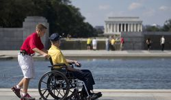 Korean War veteran Robert Olson of Iowa is pushed in his wheelchair by Zach Twedt, also from Iowa, around the National World War II Memorial in Washington on Tuesday, Oct. 1, 2013. Veterans who had traveled from across the country were allowed to visit the National World War II Memorial after it had been officially closed because of the partial government shutdown. After their visit, the memorial was closed again. The Lincoln Memorial is seen in the distance. (AP Photo/Carolyn Kaster)