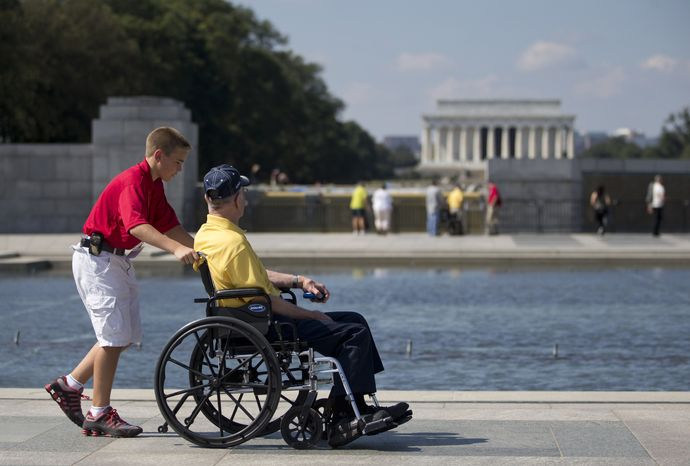 Korean War veteran Robert Olson of Iowa is pushed in his wheelchair by Zach Twedt, also from Iowa, around the National World War II Memorial in Washington on Tuesday, Oct. 1, 2013. Veterans who had traveled from across the country were allowed to visit the National