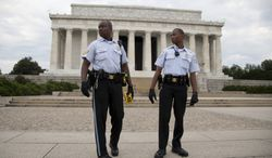 US Park Police officers stand in front of the Lincoln Memorial in Washington, Tuesday, Oct. 1, 2013, as it was closed to visitors. Congress plunged the nation into a partial government shutdown Tuesday as a long-running dispute over President Barack Obama's health care law stalled a temporary funding bill, forcing about 800,000 federal workers off the job and suspending most non-essential federal programs and services. (AP Photo/Carolyn Kaster)