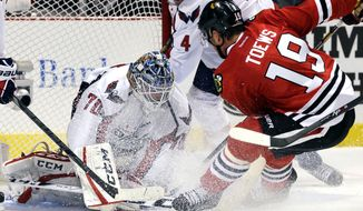Washington Capitals goalie Braden Holtby (70) saves a shot by Chicago Blackhawks' Jonathan Toews (19) during the second period of an NHL hockey game on Tuesday, Oct. 1, 2013, in Chicago. (AP Photo/Nam Y. Huh)