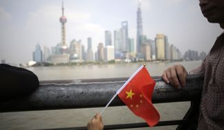 ** FILE ** A young holiday-goer waves the Chinese national flag on the first day of a weeklong National Day holidays in Shanghai, China, Tuesday, Oct. 1, 2013. This year marks the 64th anniversary of the founding of the People's Republic of China. (AP Photo/Eugene Hoshiko)
