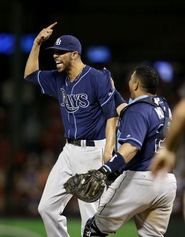 Tampa Bay Rays' David Price and Jose Molina (28) celebrate after defeating Texas Rangers 5-2 in their American League wild-card tiebreaker baseball game Monday, Sept. 30, 2013, in Arlington, Texas. (AP