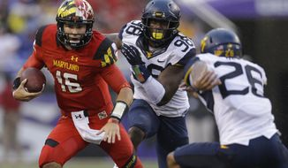 Maryland quarterback C.J. Brown, left, rushes the ball between West Virginia defensive lineman Will Clarke (98) and cornerback Travis Bell in the first half of an NCAA college football game in Baltimore, Saturday, Sept. 21, 2013. (AP Photo/Patrick Semansky)