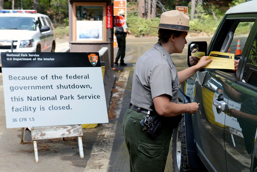** FILE ** Park Ranger Heidi Schlichting informs visitors of the closure of Yosemite National Park in California because of the government shutdown on Wednesday, Oct. 2, 2013. (AP Photo/The Fresno Bee, Craig Kohlruss)