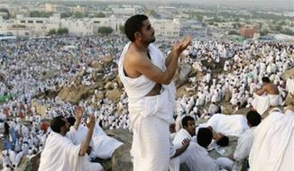 ** FILE ** Muslim pilgrims pray on a rocky hill called the Mountain of Mercy on the Plain of Arafat near the holy city of Mecca, Saudi Arabia, Oct. 25, 2012. (AP Photo/Hassan Ammar)