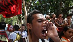 A Filipino protester shouts slogans as they march near the U.S. Embassy during a rally to oppose the planned visit of U.S. President Barack Obama in Manila, Philippines, on Wednesday Oct. 2, 2013. Obama has canceled two stops, Malaysia and Philippines, on his long-planned trip to Asia because of the partial government shutdown, the White House announced Wednesday. (AP Photo/Aaron Favila)