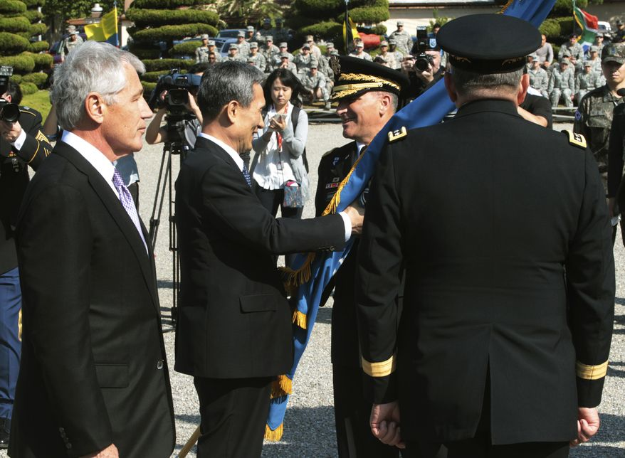 South Korean Defense Minister Kim Kwan-jin (center left) gives the South Korea-U.S. Combined Forces Command flag to the unit's incoming commander, U.S. Army Gen. Curtis Scaparrotti (center right), as U.S. Secretary of Defense Chuck Hagel (left) and the outgoing commander, U.S. Army Gen. James D. Thurman, look on during a change-of-command ceremony for the United Nations Command, Combined Forces Command and United States Forces Korea at a U.S. military base in Seoul on Wednesday, Oct. 2, 2013. (AP Photo/Ahn Young-joon)