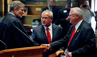 Colorado Supreme Court Chief Justice Michael Bender (left) shakes hands with Bernie Herpin as George Rivera looks on after the two Republicans were sworn in Thursday as state senators, having defeated Democratic senators in a recall over new gun restrictions in October. They replace John Morse and Angela Giron of Pueblo. (ASSOCIATED PRESS)