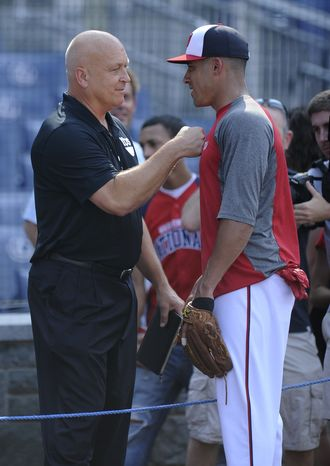 Hall of Famer Cal Ripken Jr., left, meets with Washington Nationals shortstop Ian Desmond, right, during batting practice before a baseball game against the Los Angeles Dodgers, Saturday, July 20