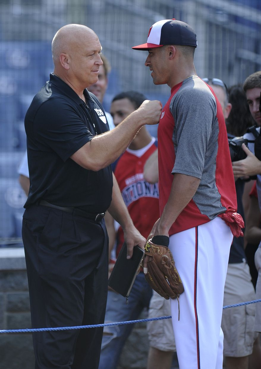 Hall of Famer Cal Ripken Jr., left, meets with Washington Nationals shortstop Ian Desmond, right, during batting practice before a baseball game against the Los Angeles Dodgers, Saturday, July 20, 2013, in Washington. (AP Photo/Nick Wass)