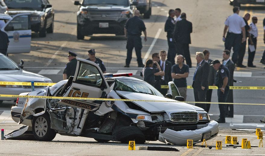 A damaged Capitol Hill police care is surrounded by crime scene tape after a car chase and shooting on Capitol Hill in Washington, Thursday, Oct. 3, 2013. A woman driving a black Infiniti with a young child inside tried to ram through a White House barricade Thursday, then led police on a chase that ended in gunfire outside the Capitol, witnesses and officials said.  (AP Photo/ Evan Vucci)