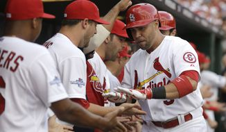 St. Louis Cardinals' Carlos Beltran, right, is congratulated in the dugout by teammates after hitting a three-run home run against the Pittsburgh Pirates in the third inning of Game 1 of baseball's National League division series on Thursday, Oct. 3, 2013, in St. Louis. (AP Photo/Jeff Roberson)