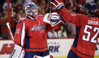 Washington Capitals goalie Michal Neuvirth (30), from the Czech Republic, celebrates with defenseman Mike Green after the shootout of an NHL hockey game against the Calgary Flames, Thursday, Oct. 3, 2013, in Washington. The Capitals won 5-4. (AP Photo/Alex Brandon)