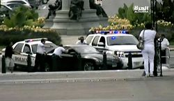 This image from video provided by Alhurra Television shows police with guns drawn surrounding a black Infiniti near the U.S. Capitol in Washington, Thursday, Oct. 3, 2013. A woman with a young child inside tried to ram through a White House barricade, then led police on a chase toward the Capitol, where police shot and killed her, witnesses and officials said. (AP Photo/Alhurra Television)