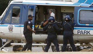 A U.S. Park Police helicopter is loaded on the Mall in Washington, Thursday, Oct. 3, 2013, with a victim from a shooting. Police say the U.S. Capitol has been put on a security lockdown amid reports of possible shots fired outside the building.  (AP Photo/Alex Brandon)