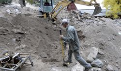 Backhoe operator Rick Benson works with Randy Walter, at center, to make a path to a propane tank while cleaning up flood damage on Thursday, Oct. 3,2013,  in Salina, Colo. The flooding damaged or destroyed nearly 1,800 homes in Colorado.  (AP Photo/The Daily Camera, Jeremy Papasso) NO SALES