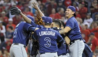 The Tampa Bay Rays celebrate after beating the Cleveland Indians 4-0 in the AL wild-card baseball game Wednesday, Oct. 2, 2013, in Cleveland. The Rays will face the Boston Red Sox in the division series starting Friday. (AP Photo/Phil Long)