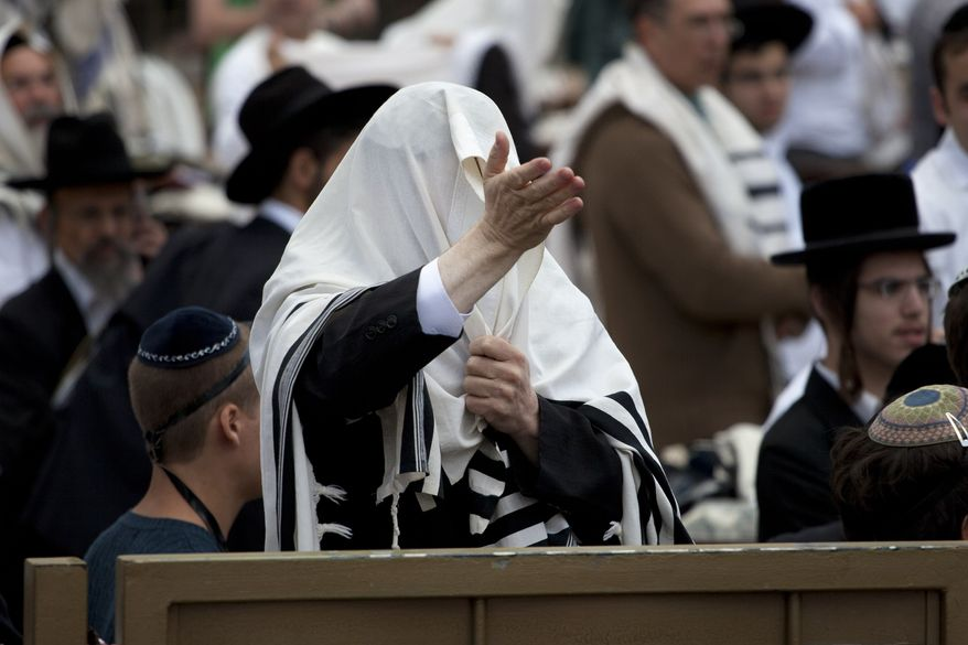 """An Ultra-Orthodox Jewish man gestures as Israeli women of the """"Women of the Wall"""" organization pray at the Western Wall, the holiest site where Jews can pray in Jerusalem's old city, Friday, Oct. 4, 2013. The group convenes monthly prayer services at the Western Wall, wearing prayer shawls and performing rituals that Ultra-Orthodox Jews believe only men are allowed to do. (AP Photo/Sebastian Scheiner)"""