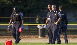 Police officers investigate at the scene on the National Mall in Washington, where, according to a fire official, a man set himself on fire Friday, Oct. 4, 2013.  The official said the man was flown by helicopter to a hospital.  (AP Photo/J. Scott Applewhite)