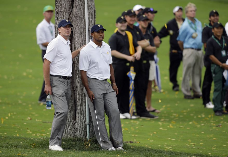 United States team player Tiger Woods, right, rests against a tree with teammate Steve Stricker on the 18th hole during the single matches at the Presidents Cup golf tournament at Muirfield Village Golf Club Sunday, Oct. 6, 2013, in Dublin, Ohio. (AP Photo/Darron Cummings)