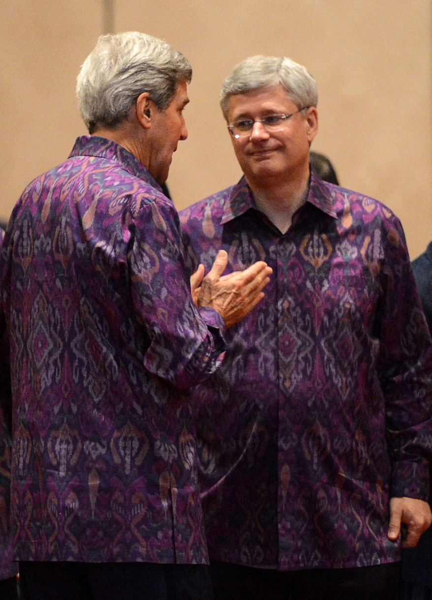 Canadian Prime Minister Stephen Harper, right, talks with United States Secretary of State John Kerry as they arrive to the Family Photo and Gala Dinner during the Asia-Pacific Economic Cooperation (APEC) summit in Bali, Indonesia, Monday, Oct. 7, 2013. (AP Photo/The Canadian Press, Sean Kilpatrick)