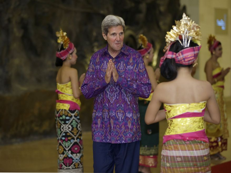 "U.S. Secretary of State John Kerry, wearing ""endek,"" a traditional Balinese woven fabrics, poses upon arrival for a dinner for leaders of the Asia-Pacific Economic Cooperation (APEC) forum in Bali, Indonesia, Monday, Oct. 7, 2013. (AP Photo/Dita Alangkarai, Pool)"
