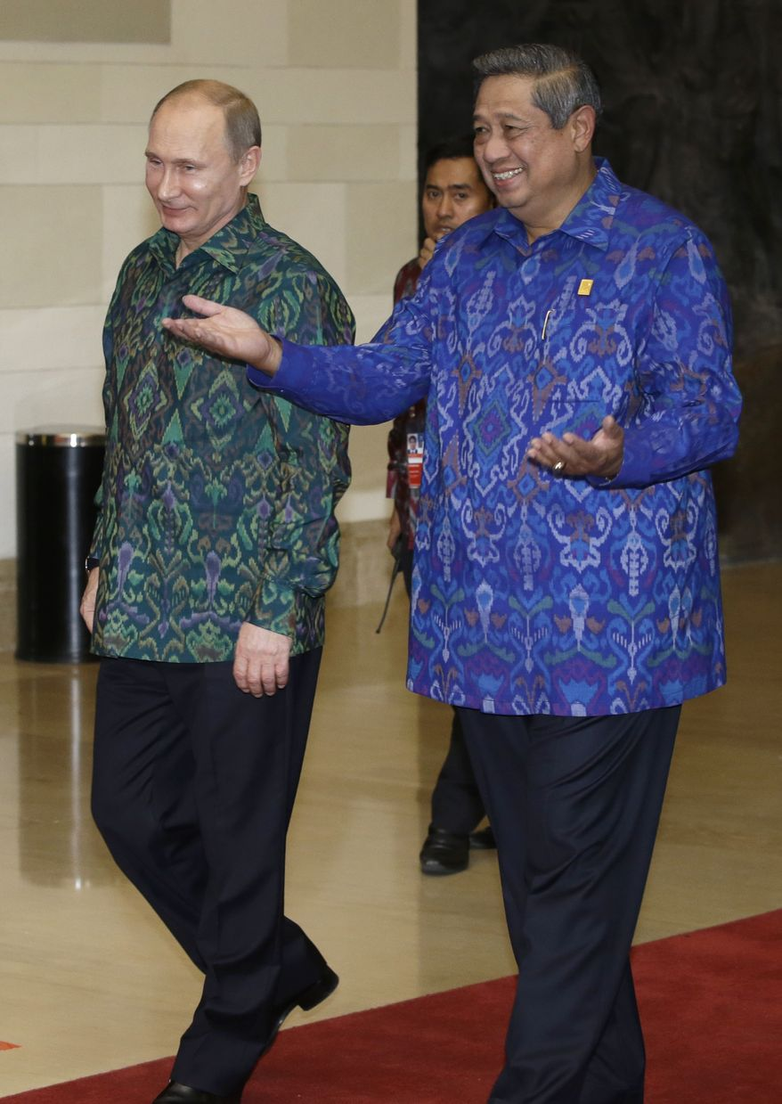"""Russian President Vladimir Putin, left, wearing """"endek,"""" a traditional Balinese woven fabrics, is escorted by Indonesian President Susilo Bambang Yudhoyono upon arrival for a dinner for leaders of the Asia-Pacific Economic Cooperation (APEC) forum in Bali, Indonesia, Monday, Oct. 7, 2013. (AP Photo/Dita Alangkarai, Pool)"""