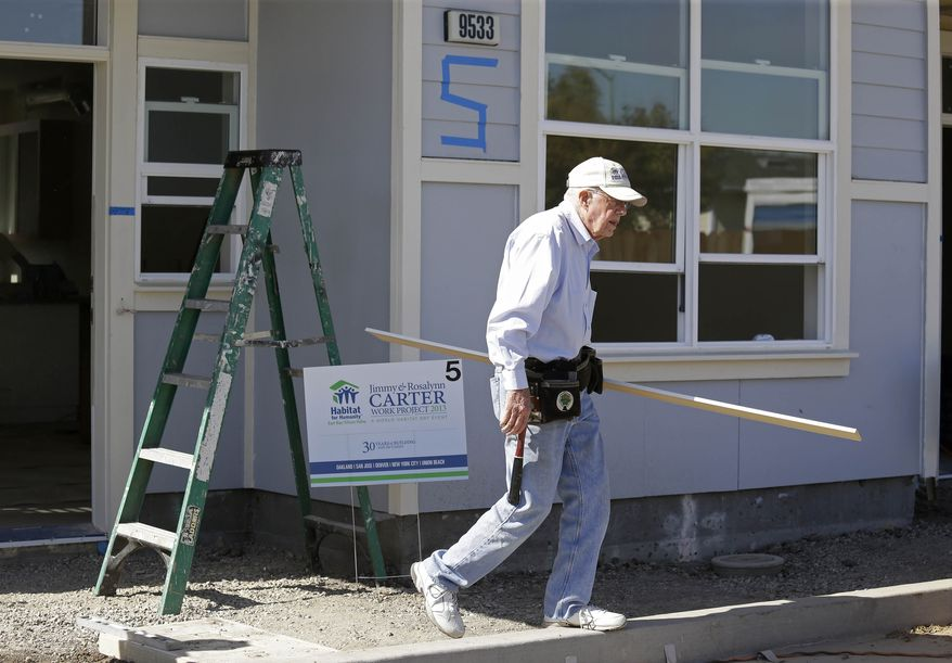 Former President Jimmy Carter walks to a saw to trim a piece of molding at a Habitat for Humanity homesite Monday, Oct. 7, 2013, in Oakland, Calif. The former President and his wife are commemorating their three-decade-long relationship with Habitat for Humanity by wielding hammers and saws in the San Francisco Bay Area. Carter said Monday that if he were back in the White House, he would work with Republicans and Democrats to secure more funding for affordable housing and urge more flexibility in resolving differences involving the critical issue. (AP Photo/Eric Risberg)