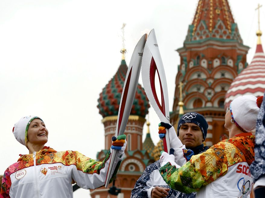 Olympic champion Anastasya Davydova, left, and the great Russian artistic gymnast Svetlana Khorkina hold their torches during a relay for the Sochi Winter Olympic Games in Moscow, Russia, Monday, Oct. 7, 2013. The St. Bazil's Cathedral is at the background.  The relay for the Winter Games, which began Monday in Moscow, will pass through many cities that showcase the historical, cultural and ethnic richness of Russia. (AP Photo/Dmitry Lovetsky)
