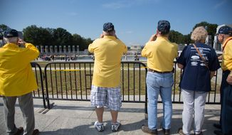 World War II veterans take photos of the National World War II Memorial from behind barricades after the National Park Service closed monuments and national parks because of the government shutdown on Tuesday, October 1, 2013, in Washington. (Andrew S. Geraci/The Washington Times)