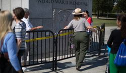 A National Park Service ranger stops a tourist from entering the World War II memorial during its closure due to the government shutdown in Washington, DC., Wednesday, October 2, 2013.  (Andrew S Geraci/The Washington Times)