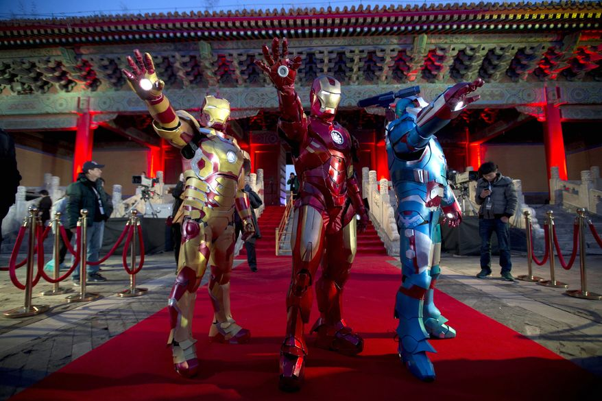 """FILE - In this Saturday, April 6, 2013 file photo, Chinese performers dressed as Iron Man pose for photos during a promotional event for the movie """"Iron Man 3"""" before its release in China in early May at the Imperial Ancestral Temple in Beijing's Forbidden City. Hong Kong Disneyland is adding an Iron Man-themed area in the hopes that the Marvel superhero's success at the Chinese box office will help draw more visitors to the underachieving resort. The park said Tuesday, Oct. 8 that the Iron Man Experience is planned to open by late 2016. (AP Photo/Andy Wong, File)"""