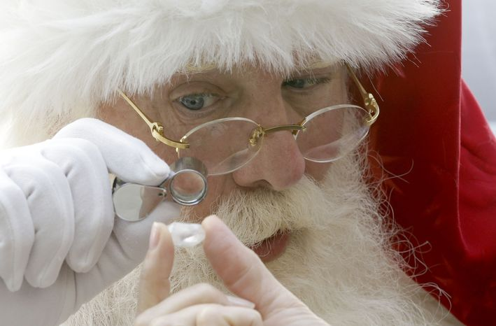 Actor Brady White portrays Santa Claus as he looks at a 25-carat rough Forevermark diamond  offered in the Neiman Marcus Christmas Book Tuesday, Oct. 8, 2013, in Dallas.  The Forevermark Ulitmate Diamond Experience on sale for $1,850,000 includes the diamond and a trip to London and Africa to trace the provenance of the stone. (AP Photo/LM Otero)
