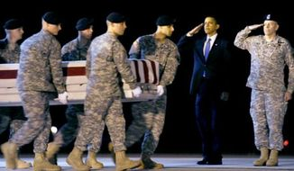 The flag-draped casket of a soldier killed in Afghanistan is returned to Dover Air Force Base in Delaware, where President Obama issued this salute. (AP photo)