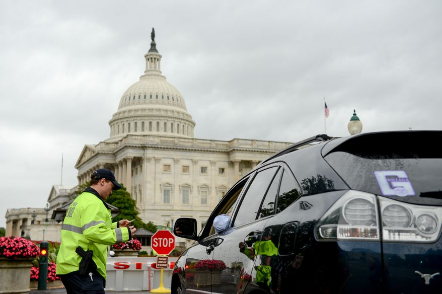A U.S. Capitol Police Officer checks a car at a security checkpoint at the U.S. Capitol Building after last week's car chase that ended in a shootout at 1st Street and Constitution Ave. NE in front of the Hart Office Building, Washington, D.C., Monday, October 7, 2013. (Andrew Harnik/The Washington Times)