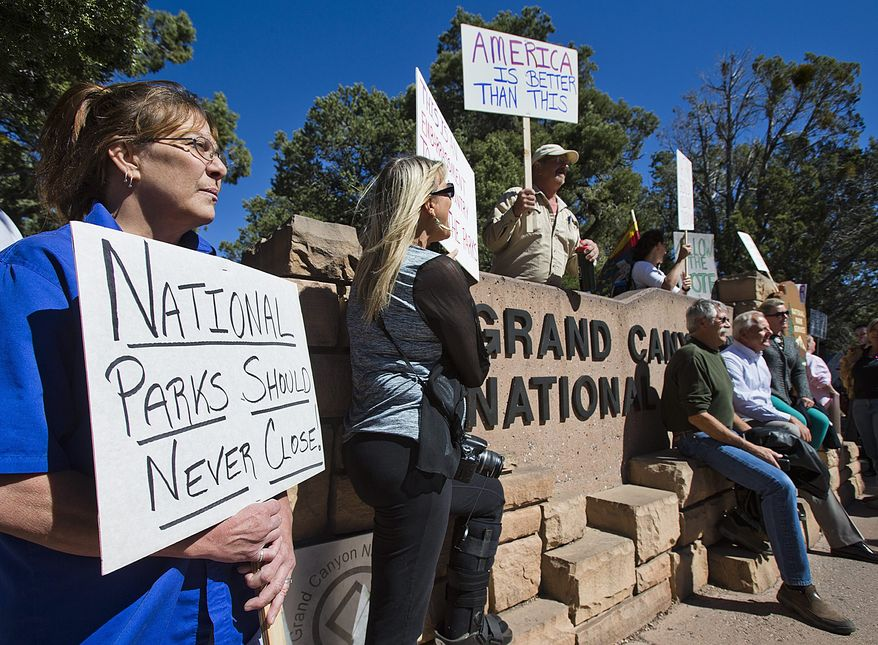 Tammy Cox (left), a worker at a Holiday Inn in Tusayan, Ariz., joins nearly 100 other protesters at the south entrance to the Grand Canyon. (Associated Press)