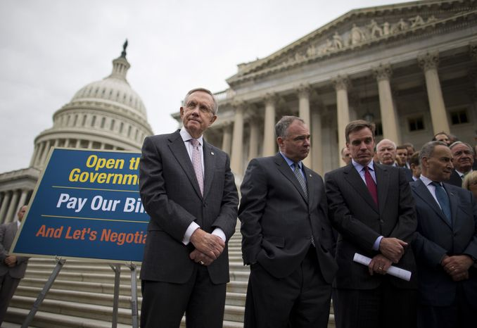 From left, Senate Majority Leader Harry Reid of Nev., Sen. Tim Kaine, D-Va., Sen. Mark Warner, D-Va., Sen. Charles Schumer, D-N.Y., and others stand on the Senate steps on Capitol Hill in Washington, Wednesday, Oct. 9, 2013, during a news conference on the ongoing budget battle. President Barack Obama was making plans to