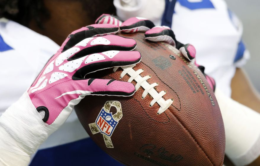 Dallas Cowboys players wear pink gloves in support of breast cancer awareness during the first quarter of an NFL football game against the Denver Broncos Sunday, Oct. 6,2013, in Arlington, Texas. (AP Photo/Tony Gutierrez)