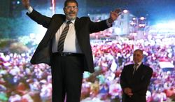 FILE - In this Sunday, May 20, 2012 file photo, then Muslim Brotherhood's presidential candidate Mohammed Morsi holds a rally in Cairo, Egypt. An Egyptian court has set Nov. 4, 2013, as the start date for the trial of ousted President Mohammed Morsi on charges of incitement to murder for the killings of opponents who were rallying outside his palace while he was in office. Morsi, ousted in a popularly-backed military coup in July, has been held incommunicado since. (AP Photo/Fredrik Persson, File)