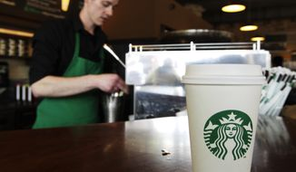 ** FILE ** A Starbucks drink awaits customer pickup as barista Josh Barrow prepares another in Seattle on  Friday, April 27, 2012. (AP Photo/Ted S. Warren)