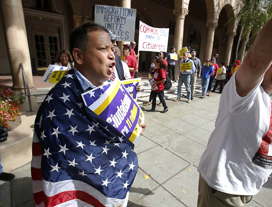Wearing an American flag, Lino Pedres, joined others in a march outside the building where the state Republican Party Headquarters is located calling on the GOP to support immigration reform, in Sacramento, Calif., Tuesday, Oct. 8, 2013. More than two dozen immigrant rights advocates, students, labor and community activists gathered for the protest. (AP Photo/Rich Pedroncelli)