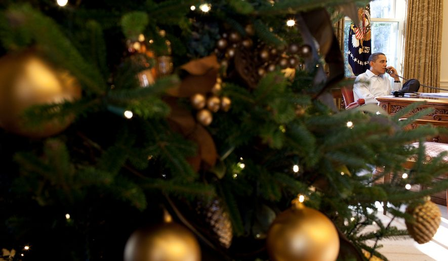 A Christmas tree frames President Barack Obama as he talks on the phone in the Oval Office, Dec. 12, 2009. (Official White House Photo by Pete Souza)