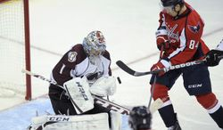 Washington Capitals center Mikhail Grabovski, right, fights for the puck against Colorado Avalanche goalie Semyon Varlamov (1), of Russia, during the third period an NHL hockey game, Saturday, Oct. 12, 2013, in Washington. The Avalanche won 5-1. (AP Photo/Nick Wass)